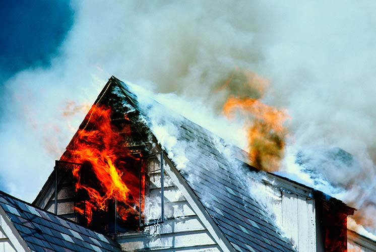 Smoke and fire spewing from a peaked house roof.